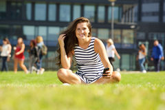 Young woman sitting on grass outside holding mobile Royalty Free Stock Image