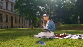 Young woman sitting on the grass in the park, holding an open notebook, looking away and smiling. Happy student concept. stock video