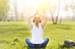 Young woman sitting on grass in Park and meditating and listenin Royalty Free Stock Images