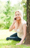 Young woman sitting on grass with phone Royalty Free Stock Images