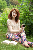 Young woman sitting on grass. Smiling young woman using a phone and relaxing at park Stock Photos