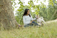 A young woman sitting on the grass, stroking her dog Stock Photo