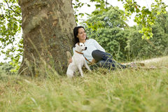 A young woman sitting on the grass, stroking her dog Stock Photography