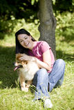 A young woman sitting on the grass, stroking her dog Stock Photos
