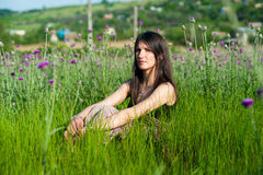 Young woman sitting in grass Stock Photo