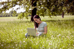 A young woman sitting on the grass using a laptop Royalty Free Stock Image