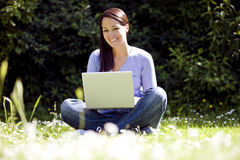 A young woman sitting on the grass, using a laptop Royalty Free Stock Photo