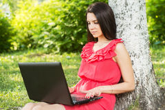 Young woman sitting on the grass, using laptop and typing Stock Images