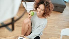 Young woman sitting with green apple at home and smiling at camera. Young cheerful healthy Afro American woman sitting with green apple at home and smiling at royalty free stock photos
