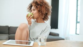 Young woman sitting with green apple at home and smiling at camera. Young cheerful healthy Afro American woman sitting with green apple at home and smiling at royalty free stock photo