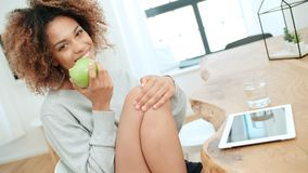 Young woman sitting with green apple at home and smiling at camera. Young cheerful healthy Afro American woman sitting with green apple at home and smiling at stock image