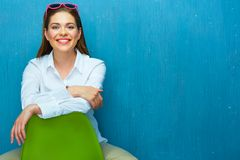 Young woman sitting on green chair. Stock Images