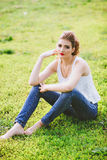 Young woman sitting on a green football field, dressed in blue jeans, a white t-shirt. Red lips. Royalty Free Stock Photo
