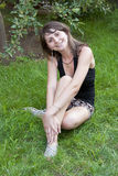 Young woman sitting on the green grass Royalty Free Stock Image