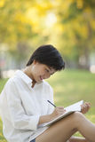 Young woman sitting on green grass park with pencil and note boo Stock Photos