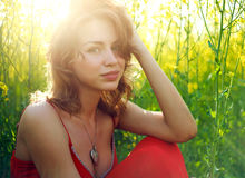 Young woman sitting in green grass in sunlight Royalty Free Stock Photos