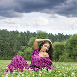 Young woman sitting on a green lawn Royalty Free Stock Photos