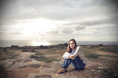 Young woman sitting on the ground Stock Photos