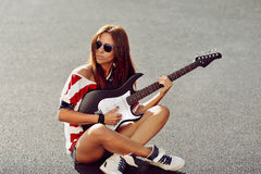 Young woman sitting on a ground and playing guitar Royalty Free Stock Image