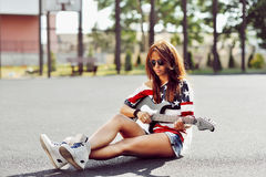 Young woman sitting on a ground and playing guitar Stock Image