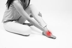 Young woman sitting on ground touching her injured foot Stock Images