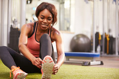 Young woman sitting in a gym tying her shoelaces, horizontal Stock Photos
