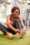 Young woman sitting in a gym tying her shoelaces, vertical Stock Photo
