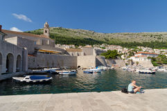 Young woman sitting in the harbor of Dubrovnik. DUBROVNIK, CROATIA - MAY 15, 2013: Young woman sitting in the harbor of Dubrovnik, Croatia. On 15 May 2013 in Royalty Free Stock Image