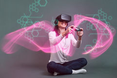 Young woman sitting and having fun playing a virtual reality vid Stock Photos