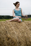 Young woman sitting at the haystack Stock Photography