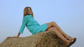 Young woman sitting on a haystack and looking to the camera. stock video