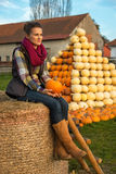 Young woman sitting on haystack with pumpkin Royalty Free Stock Images