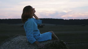 Young woman sitting on a haystack during sunset. stock video
