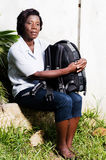 Young woman sitting with her bag on her knee Stock Photo