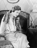Young woman sitting on her bed in the bed room, speaking on the telephone  (All persons depicted are not longer living and no esta Royalty Free Stock Image