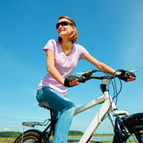 Young woman is sitting on her bicycle Royalty Free Stock Photo