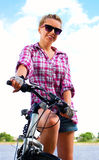 Young woman is sitting on her bicycle, outdoor shoot Royalty Free Stock Photos