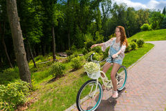 Young woman sitting on her bicycle in a park Stock Photography
