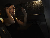 Young woman sitting in her car and checking her hair in the phone before going out on a rainy night in Beijing Royalty Free Stock Images