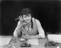 Young woman sitting at her desk in an office with a telephone in her hands. (All persons depicted are no longer living and no estate exists. Supplier grants Stock Images