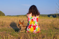 Young woman sitting with her dog. Back to camera on the meadow at sunset royalty free stock image