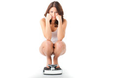 Young woman sitting on her haunches on a scale Royalty Free Stock Photos
