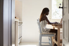 Young woman sitting in her kitchen using laptop computer Royalty Free Stock Photos