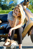 Young woman sitting on her motor scooter Royalty Free Stock Images