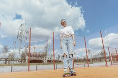 Young woman skating with her sons at playground. Happy family concept. royalty free stock images