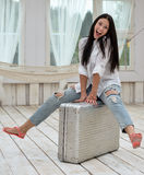 Young woman sitting on her suitcase at home Royalty Free Stock Images