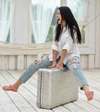 Young woman sitting on her suitcase at home Stock Photo