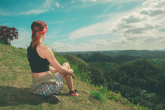 Young woman sitting on a hill and admiring view Royalty Free Stock Photos