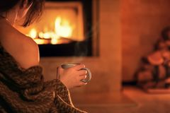 Young woman sitting at home by the fireplace . royalty free stock image