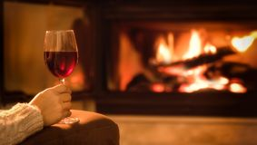 Young woman sitting at home by the fireplace . Young woman sitting at home by the fireplace and drinking a red wine Royalty Free Stock Photography